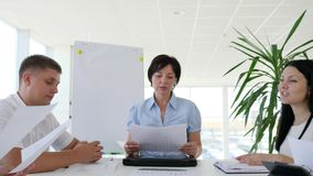 Business meeting of collaborators at desk with documents in hand in boardroom. With large windows stock footage