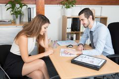 Business meeting at desk in office beauty businesswoman with handsome businessman. Teamwork in business meeting at desk in office beauty businesswoman with royalty free stock image