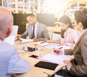 Business meeting between four professional entrepreneurial executives indoors. Indoor meeting between 4 business executives in a warm creative environment Royalty Free Stock Photography