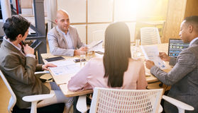 Business meeting between four professional entrepreneurial executives indoors. Indoor meeting between 4 business executives in a warm creative environment royalty free stock photo