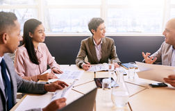 Business meeting between four professional executives in conference room. Four business professionals conducting a meeting in a bright modern conference room royalty free stock photos