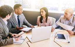 Business meeting between four professional executives in conference room. Four business professionals conducting a meeting in a bright modern conference room royalty free stock photography