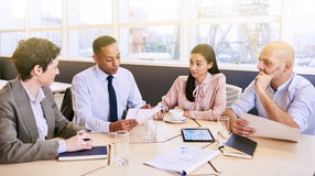 Business meeting between four professional executives in conference room. Four business professionals conducting a meeting in a bright modern conference room stock photography