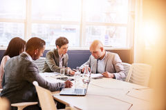 Business meeting between four professional executives in conference room. Four business professionals conducting a meeting in a bright modern conference room stock image