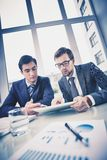 Business meeting. Image of two young businessmen discussing document in touchpad at meeting Stock Images