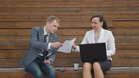 Business meeting of man and woman outside office. In time of lunch break. They discussing ideas and financial data. Slow motion. Lifestyle and business concept stock video footage
