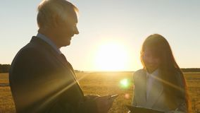 Business meeting men and women in the park. Businessman and businesswoman with tablet negotiate at sunset and laugh. Business meeting men and women in park stock video