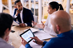 Business meeting with modern tablet to view real time data. Diverse group of four business individuals listening to a young female partner busy talking to them Stock Photo