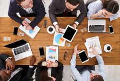 Business meeting. Multiethnic emploees team discuss the report in office, top view of wooden table Royalty Free Stock Photos