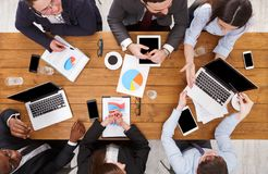 Business meeting. Multiethnic emploees team discuss the results of work in office, top view of wooden table Royalty Free Stock Images