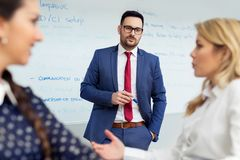 Business meeting at office. Handsome man presenting charts on whiteboard to team. Royalty Free Stock Photography