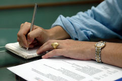Business meeting notes. Close-up shot of a business woman's hands writing or taking notes amidst papers and reports stock images