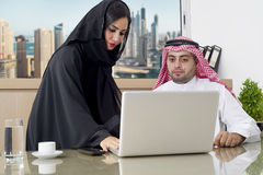 Business Meeting in office , arabian businessman & arabian Secretary wearing hijab working on laptop.  Royalty Free Stock Photos