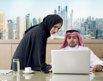 Business Meeting in office , arabian businessman & arabian Secretary wearing hijab working on laptop Stock Image