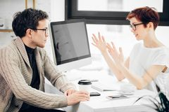 Advisor businesswoman sitting at office in front of computer and consulting man stock image