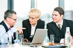 Business - meeting in office, people working with document. Business - meeting in office, the businesspeople with boss and team are discussing a document on stock photography