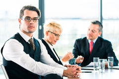 Business - meeting in office, people working with document. Business - meeting in office, the businesspeople are discussing a document on Laptop computer and stock image