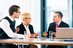 Business - meeting in office, people working with document. Business - meeting in office, the businesspeople are discussing a document on Laptop computer and royalty free stock image
