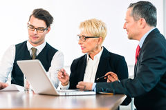 Business - meeting in office, people working with document. Business - meeting in office, the businesspeople are discussing a document on Laptop computer and stock images