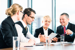Business - meeting in office, people working with document. Business - meeting in office, the businesspeople or lawyers in team are discussing a document on stock image