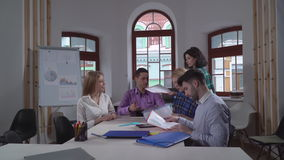 Business meeting in the office. Young casual group of people sitting in the boardroom. Brunette giving folders with presentation or report coworkers stock video footage
