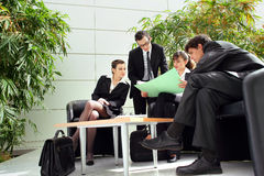 Business meeting outdoors. Two young men and two young women sitting aroung a table outside, working together Royalty Free Stock Photo