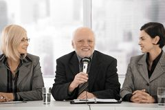 Business meeting, senior man with microphone royalty free stock photography