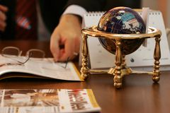 Business meeting still life. Close up of a globe on a wooden table with businessman's hands, glasses and business magazines. the globe shows the USA Royalty Free Stock Photo