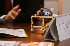 Business meeting still life. Close up of a globe on a wooden table with businessman's hands, glasses and business magazines. the globe shows the USA Stock Photography
