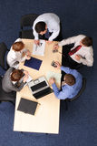 Business meeting - strategy. Businesspeople gathered around a table for a meeting, brainstorming. Aerial shot taken from directly above the table royalty free stock photography