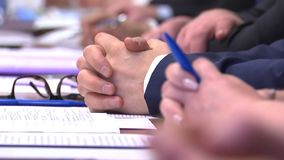 Business meeting, table discussions, teamwork. Business meeting at the table, people holding pens, glasses, notebooks stock footage
