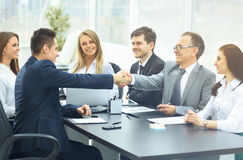 Business meeting. At the table and handshake of business partners Stock Image