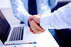 Business meeting at the table shaking hands Stock Photo