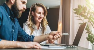Business meeting. Teamwork. Businesswoman and businessman sitting at table in front of laptop and working. E-learning. Business meeting. Teamwork. Businesswoman Royalty Free Stock Images