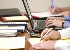 Business Meeting. Three business people attend a meeting with laptop, phone, pen, and pad Royalty Free Stock Photography