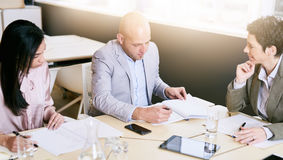 Business meeting between three professional partners early in the morning stock image
