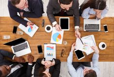 Business meeting top view. Multiethnic emploees listen to the report in office, top view of wooden table Stock Photo