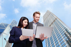 Business meeting. Two managers discussing on tablet computer with city background Stock Photography