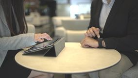 A business meeting hands using a tablet with stats. A business meeting using a tablet and smartwatch with stats and graphs stock footage