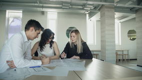 Business meeting of women man sitting inside office. Nice blonde woman with straight hair, black shirt writes notes about business ideas indoors. Building stock footage