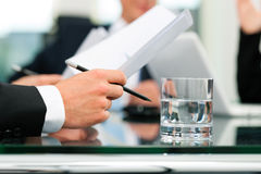 Business meeting with work on contract. Business - meeting in an office; lawyers or attorneys (only hands) discussing a document or contract agreement Royalty Free Stock Photography