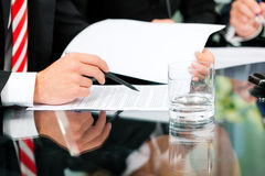 Business meeting with work on contract. Business - meeting in an office; lawyers or attorneys (only hands) discussing a document or contract agreement Royalty Free Stock Photo