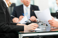 Business meeting with work on contract. Business - meeting in an office, lawyers or attorneys discussing a document or contract agreement Royalty Free Stock Photos