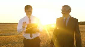 Business meeting with working partner in the park at sunset. Businessmen are discussing teamwork plan in bright sunshine. Business meeting with working partner stock video footage
