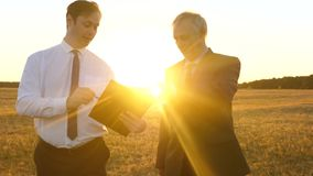Business meeting with working partner in the park at sunset. Businessmen are discussing teamwork plan in bright sunshine