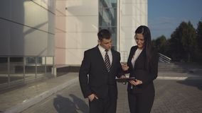 Business people while working near office building. Business meeting. Young beautiful businesswoman talks and shows documents to young male employee outdoors stock video footage