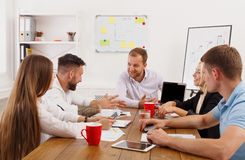 Business meeting. Young hipsters businessmen and women at modern. Business meeting. Young happy businessmen and women at modern office, team corporate discussion Royalty Free Stock Photo
