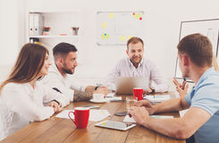 Business meeting. Young hipsters businessmen and women at modern. Business meeting. Young happy businessmen and women at modern office, team friendly discussion Stock Photography