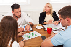 Business meeting. Young hipsters businessmen and women at modern office. Business meeting, analyzing sales. Young hipsters businessmen and women at modern office Stock Photo