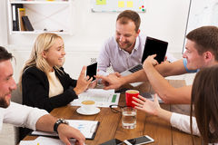 Business meeting. Young hipsters businessmen and women at modern office. Business meeting. Young happy businessmen and women at modern office, discuss digital Royalty Free Stock Photo